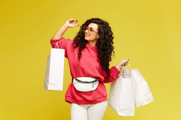 Young happy woman in a pink hoodie and modish sunglasses posing with shopping bags over yellow background, isolated with copy space