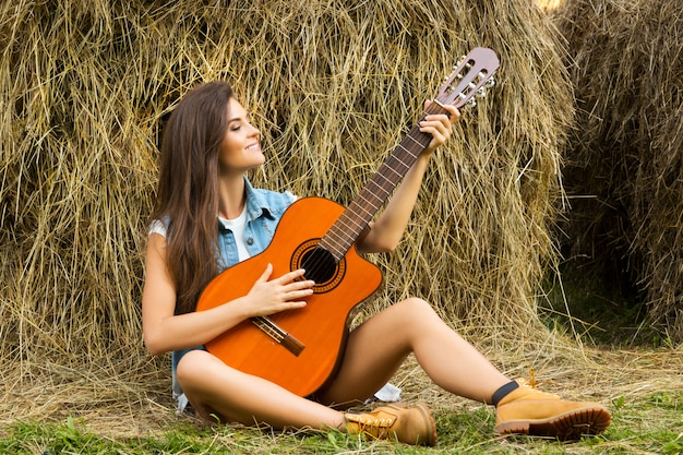 Young and happy woman playing guitar in the village