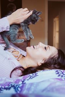 優しい愛の子猫と遊ぶ若い幸せな女。動物愛好家のライフスタイル。