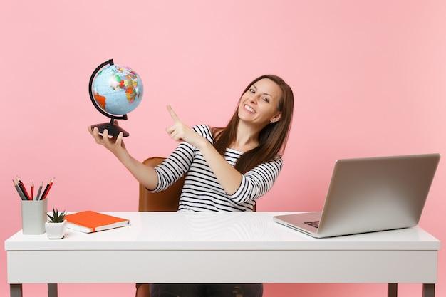 地球を指して、座って休暇を計画し、パステルピンクの背景に分離された現代的なpcラップトップで白い机のオフィスで働く若い幸せな女性。業績ビジネスキャリア。スペースをコピーします。
