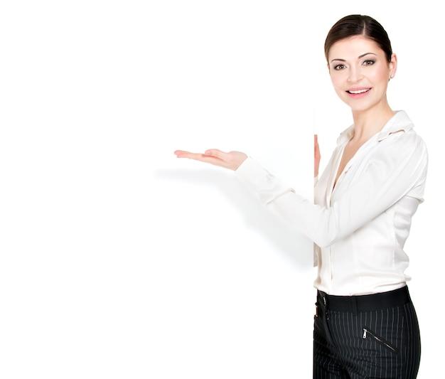 La giovane donna felice indica sulla bandiera in bianco bianca -.