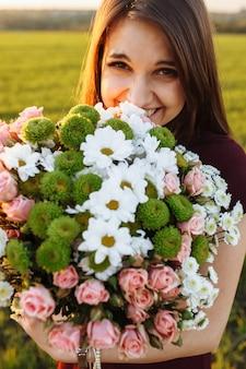 Молодая счастливая женщина позирует с большим букетом, на фоне заката на поле