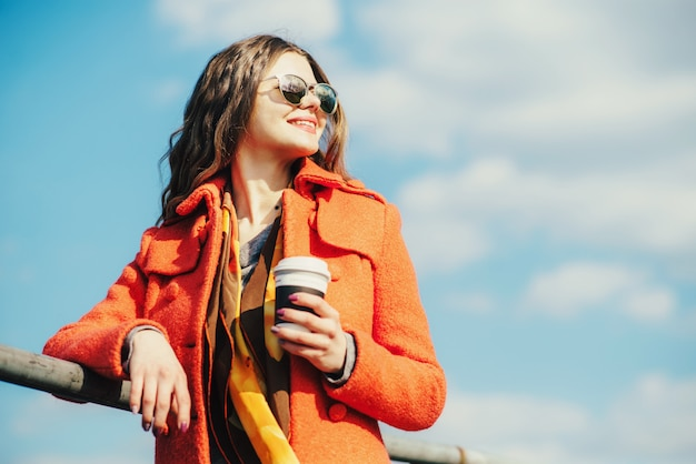 Young happy woman in red coat and sunglasses with coffee standing near the waterat the park