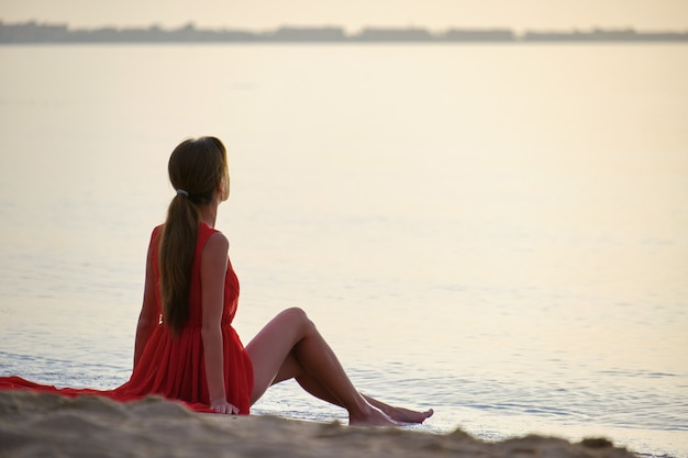 Young happy woman in red dress relaxing on sandy beach by seaside enjoying warm tropical morning.