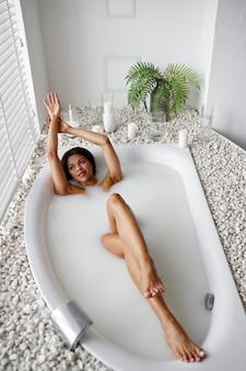 若い幸せな女性、ミルクとお風呂でリラックス。バスタブの女性、スパの美容とヘルスケア、バスルームのウェルネストリートメント、背景の小石とキャンドル