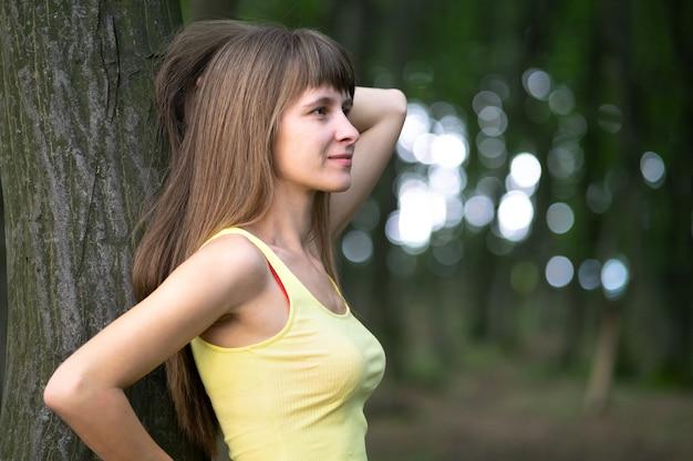 여름 공원에서 큰 나무 줄기에 기대어 휴식을 취하는 젊은 행복한 여자.