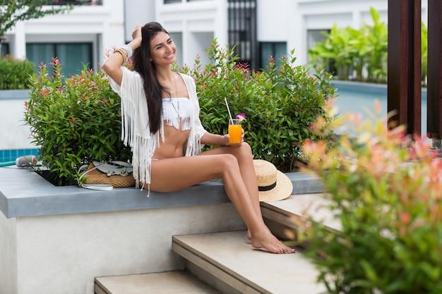Giovane donna felice rilassante con gustoso succo d'arancia fresco in abito tropicale boho alla moda durante le sue vacanze