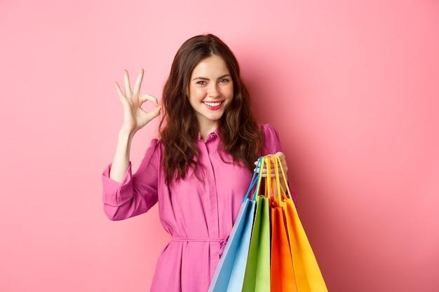 若い幸せな女性の買い物客は大丈夫な兆候を示し、良い割引に満足し、販売中のスタッフを購入し、買い物袋を持って、満足している、ピンクの壁を笑っています。