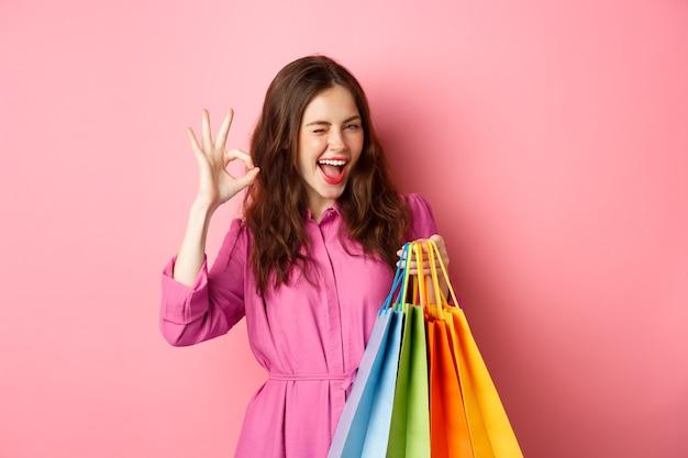 若い幸せな女性の買い物客は、大丈夫な兆候を示し、良い割引に満足してウィンクし、セール中のスタッフを購入し、買い物袋を持って、満足しているピンクの壁に微笑んでいます。