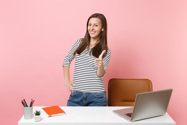 パステルピンクの背景に分離された現代的なpcラップトップで親指を上げて、仕事と白い机の近くに立っている若い幸せな女性。業績ビジネスキャリアコンセプト。広告用のスペースをコピーします。