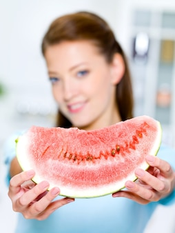 La giovane donna felice mostra un'anguria rossa