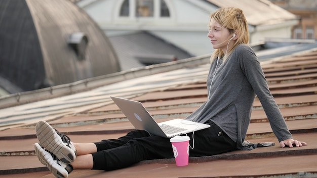 若い幸せな女性は屋上でコーヒーと一緒に座っています
