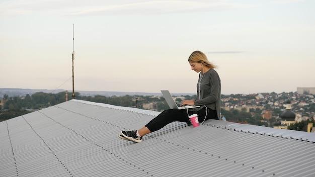 若い幸せな女性はコーヒーと一緒に座ってラップトップを使用し、屋上でヘッドフォンで音楽を聴きます