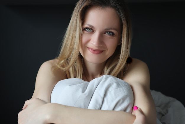 Молодая счастливая женщина сидит в постели и улыбается