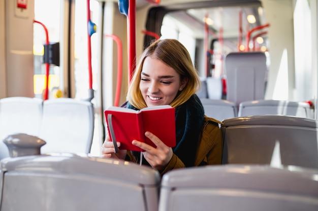 Молодая счастливая женщина сидит в городском автобусе и читает книгу