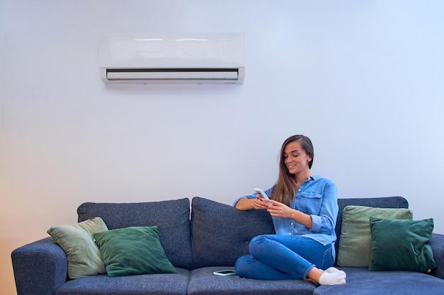 Молодая счастливая женщина сидит на диване под кондиционером и регулирует комфортную температуру с помощью пульта дистанционного управления в современном доме