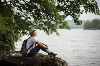 Young happy woman sitting with backpack enjoy the nature after hike.