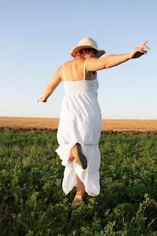 야외 필드에서 건너뛰는 젊은 행복 한 여자