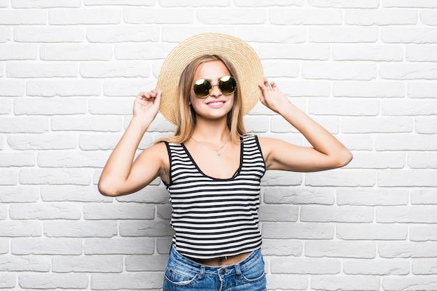 Молодая счастливая женщина улыбается в солнечных очках и летней шляпе над белой кирпичной стеной