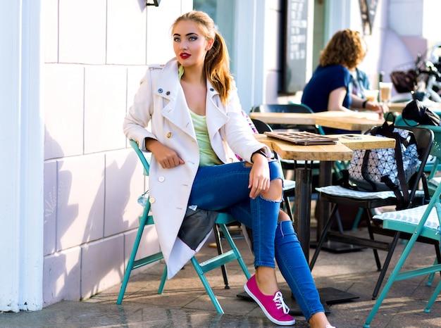 Giovane donna felice sorridente e rilassante alla terrazza del caffè della città, tempo soleggiato, trucco luminoso, abbigliamento casual elegante, vacanze, viaggi, vacanze, gioia.