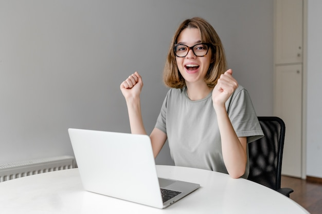 Young happy woman smiling sitting with laptop in the apartment won the prize