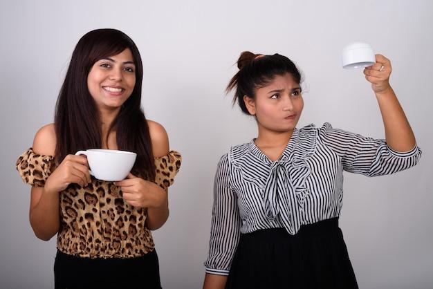 빈 커피 잔을 거꾸로 들고 어린 십 대 소녀와 함께 커피 잔을 들고 웃 고 젊은 행복 한 여자.