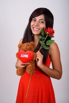 Молодая счастливая женщина улыбается, держа красную розу и плюшевого мишку с сердцем и любовным знаком, готовым на день святого валентина.