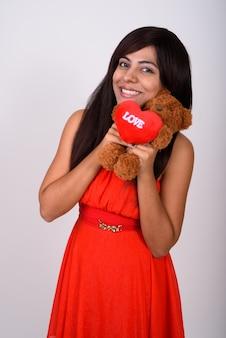 Молодая счастливая женщина улыбается, держа плюшевого мишку с сердцем и знаком любви, готовым к дню святого валентина