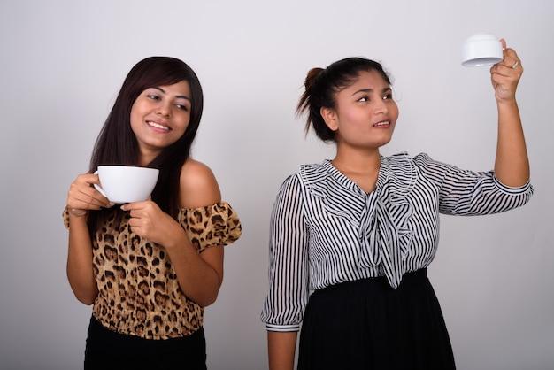 생각 하 고 빈 커피 컵을 거꾸로 들고 젊은 십 대 소녀와 함께 커피 컵을 들고 웃 고 젊은 행복 한 여자.