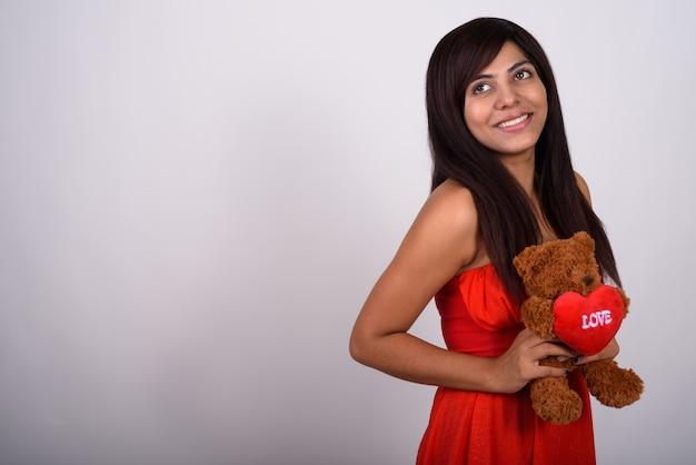 Молодая счастливая женщина улыбается, думая и держа плюшевого мишку с сердцем и любовным знаком, готовым к дню святого валентина.