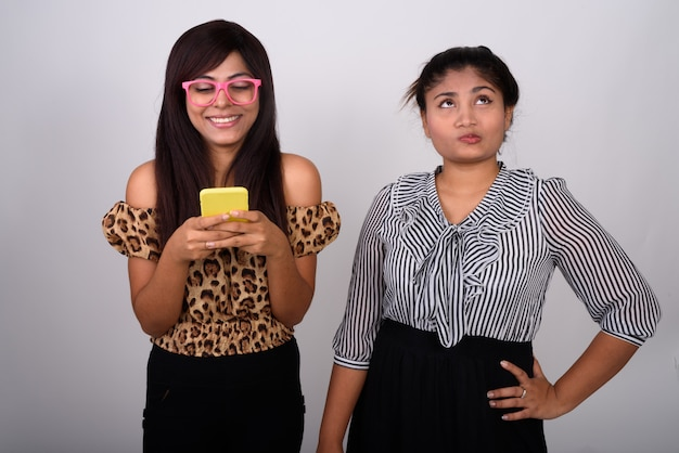 Young happy woman smiling while using mobile phone and wearing eyeglasses with young teenage girl thinking and looking annoyed   .