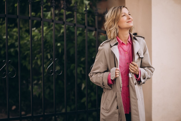 Young happy woman in spring coat out in the city