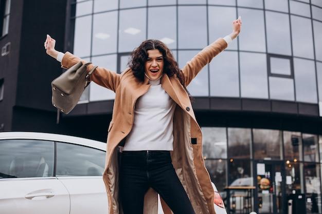 Giovane donna felice in piedi vicino alla macchina