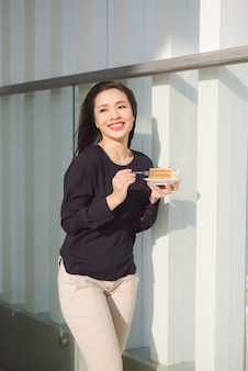 젊은 행복 한 여자는 아침에 접시 케이크와 함께 호텔의 테라스에 선다. 좋은 분위기에 꽤 아시아 소녀와 모험을위한 준비가되어 있습니다.