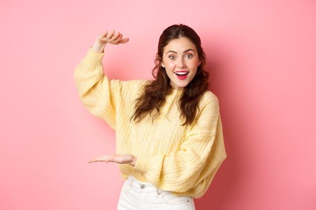 젊은 행복 한 여자 카메라를 응시 하 고, 큰 개체를 보여주는, 분홍색 벽에 서 서 복사 공간에 그녀의 손으로 제쳐두고 로고 또는 제품을 들고.