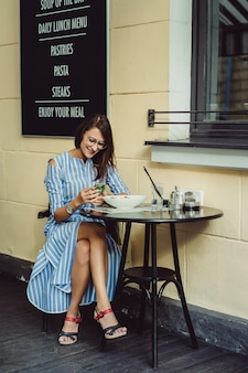 Young happy woman in a street cafe smiling laughs drinking coffee on a terrace
