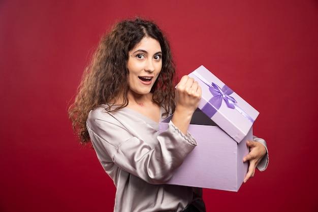 젊은 행복 한 여자는 그녀의 선물에 대해 놀 랐 다.