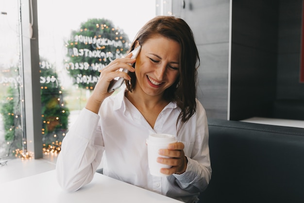 커피숍에서 휴대전화로 통화하는 젊은 행복한 여성, 점심시간에 카페에 앉아 휴대전화로 통화하는 아름다운 미소를 가진 여성