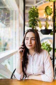 モダンな喫茶店のインテリアに一人で座っている間、友人と携帯電話で話している若い幸せな女性、夏の日を歩いた後リラックスしながら携帯電話で呼び出す笑顔の流行に敏感な女の子