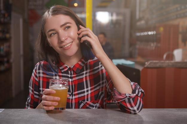 パブでクラフトビールを飲みながら電話で話している若い幸せな女性