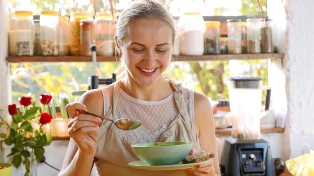 Молодая счастливая женщина, дегустация, просто готовит еду на кухне.