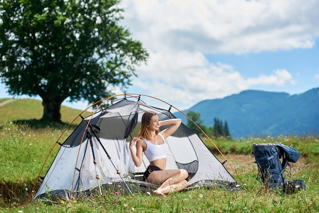 Young happy woman tourist posing at tent entrance beside backpack and trekking sticks, on the top of a hill against blue sky, big tree and clouds, smiling, looking away. camping lifestyle concept