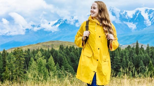배낭 젊은 행복 한 여자 관광은 그의 얼굴에 미소와 함께 산에 서있다. 텍스트 배치