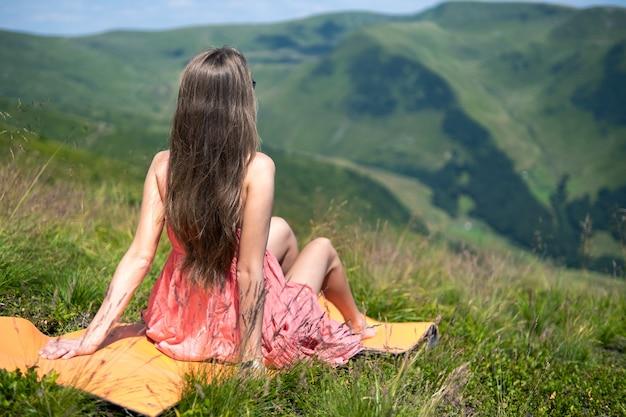 빨간 드레스를 입은 젊은 행복한 여성 여행자는 자연의 전망을 즐기는 여름 산에서 바람이 부는 날 푸른 잔디 언덕에서 쉬고 있습니다.