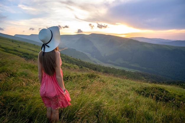 바람이 부는 저녁, 여름 산에서 해질녘 자연의 전망을 즐기며 풀이 무성한 언덕에 빨간 드레스를 입은 젊은 행복한 여성 여행자.