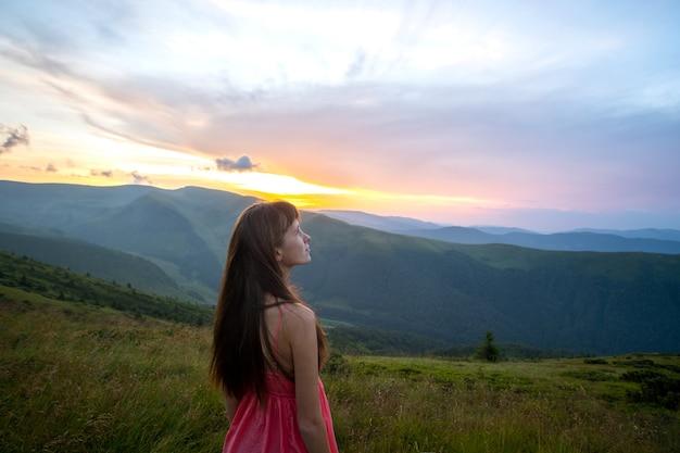 바람이 부는 저녁에 풀밭 언덕에 빨간 드레스를 입은 젊은 행복한 여성 여행자가 해질녘 자연의 전망을 즐기고 있습니다.