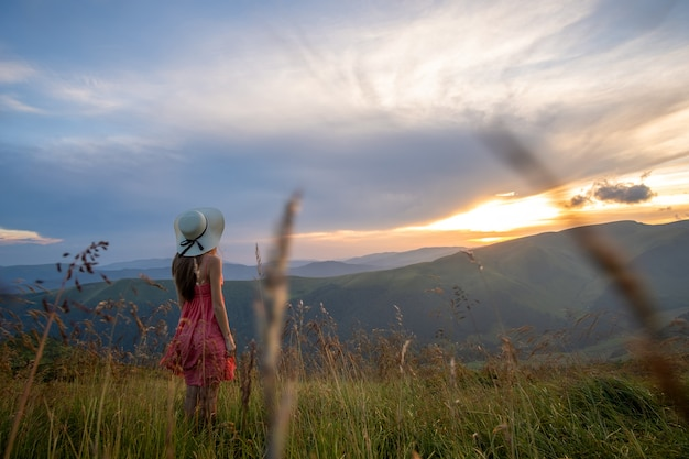 日没時の自然の景色を楽しむ夏の山々の風の強い夜に草が茂った丘の中腹に立っている赤いドレスを着た若い幸せな女性旅行者。
