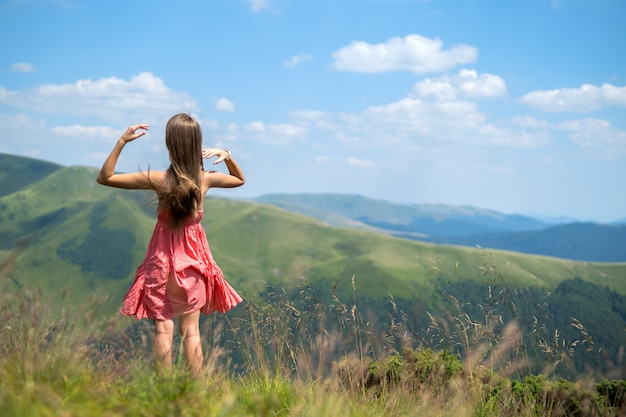 Young happy woman traveler in red dress standing on green grassy hillside on a windy day in summer mountains enjoying view of nature.