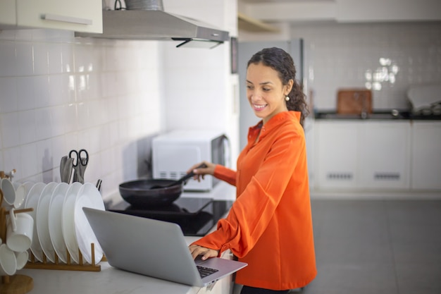 Young happy woman using laptop while preparing dinner in the kitchen.