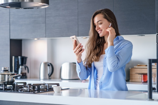 Young happy woman using smartphone and white wireless earphones for listening music and audio book in the kitchen at home. modern mobile people